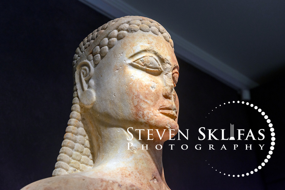 6th century BC marble statue of a naked athletic youth (Kouros) at the Kerameikos museum. Athens. Greece. Found buried near the Sacred gate in 2002, the archaic era statue would have served as a votive offering or funerary sculpture and is largely intact. In complete form it would have stood 2.10 metres or six feet, six inches tall. Serving as a burial ground as long ago as the 12th century BC, Kerameikos located in the ancient neighbourhood of potters contains part of the ancient city walls and the Dipylon, the main gate of Ancient Athens at a junction of the Sacred Way and Panathenaic Way. It served as a burial ground for the richest and most distinguished citizens of the city.