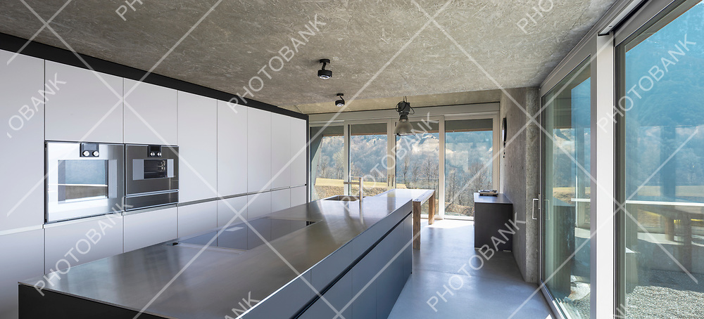 Modern white kitchen with large island, induction hob, two ovens, sink and stainless steel top. Large windows overlooking the nature of Switzerland. Nobody inside