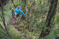 Mountain biker in mid-air jump over heap of rocks while other biker following