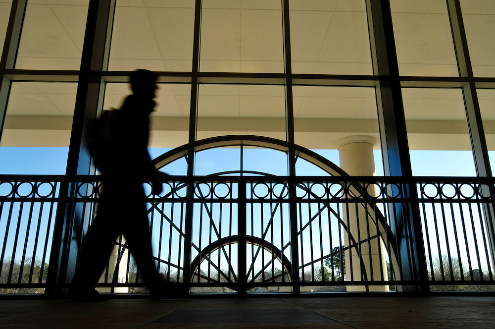 A student is silhouetted as he walks past the windows in the UCA College of Business building.