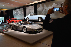 """© Licensed to London News Pictures. 14/11/2017. London, UK.  A visitor photographs (front to back) A Ferrari Testarossa Spyder, 1986, commissioned by Gianni Agnelli to commemorate his 20th anniversary as Chairman of Fiat, a Ferrari 275 GTB/4, 1967, and a Ferrari F40, 1987, built to celebrate the 40th anniversary of Ferrari.  Preview of """"Ferrari: Under the Skin"""", an exhibition at the Design Museum to mark the 70th anniversary of Ferrari.  Over GBP140m worth of Ferraris are on display from private collections including Michael Schumacher's 2000 F1 winning car.  The exhibition runs 15 November to 15 April 2018.  Photo credit: Stephen Chung/LNP"""