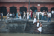 The sons of the man who died wash his remaining ashes into the river after the body has been cremated.  They are at the Pasupatinatha Temple in Kathmandu, Nepal.