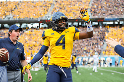 Sep 22, 2018; Morgantown, WV, USA; West Virginia Mountaineers safety Josh Norwood (4) celebrates after a turnover during the third quarter against the Kansas State Wildcats at Mountaineer Field at Milan Puskar Stadium. Mandatory Credit: Ben Queen-USA TODAY Sports