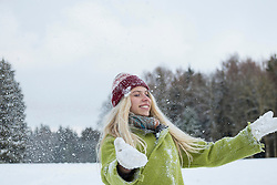 Teenage girl playing with snow in landscape, Bavaria, Germany