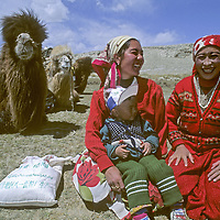Nomadic Kyrgyz women share a laugh while traveling with their Bactrian camels in the Pamir Mountains of Xinjiang, China.
