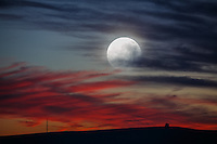The June super moon appears to  rise through sunset clouds in this double exposure made in the Palouse Region of Washington State