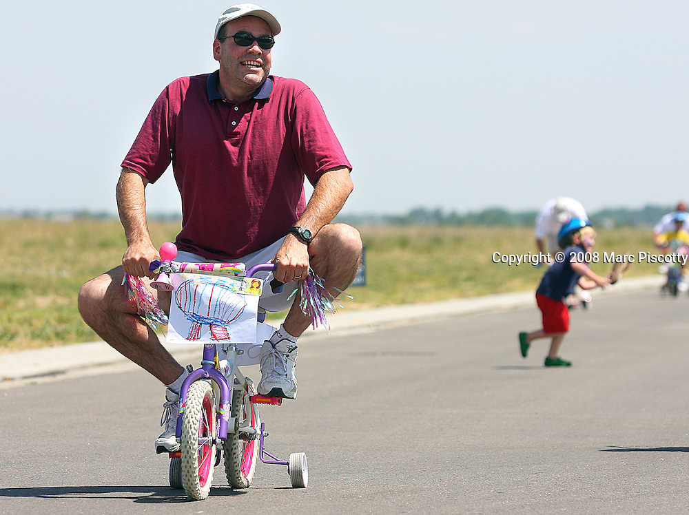 SHOT 7/5/08 11:25:22 AM - Clay Daughtrey (left, in red) makes his way towards the finish line during the parents' race at the Fifth Annual Reunion Red, White and Blue Kids' Bike Parade at Reunion Homes in Commerce City. The event features a parade of bikes by more than 100 local children many of whom decorate their rides in the colors of the July 4th holiday. The event also included an adult race on their kids' bikes for bragging rights and fun. Daughtrey jokingly said he was afraid he was going to break his daughter's bike..(Photo by Marc Piscotty / © 2008)