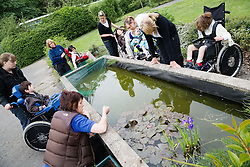 Physically disabled children out on nature walk; studying pond life,