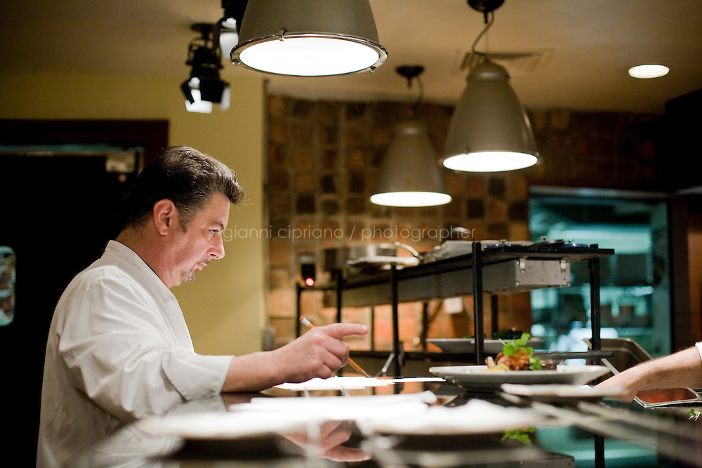 """11 December, 2008. New York, NY. Waldy Malouf waits for the orders at the kitchen of the Beacon restaurant. He is """"on stage"""" for a small birthday party of six people in the open kitchen of Beacon's dining room, a New York restaurant. Several restaurants offer special seatings with their celebrity chefs.<br /> <br /> ©2008 Gianni Cipriano for The New York Times<br /> cell. +1 646 465 2168 (USA)<br /> cell. +1 328 567 7923 (Italy)<br /> gianni@giannicipriano.com<br /> www.giannicipriano.com"""
