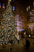 People pose for photographs in front of the Christmas tree in the courtyard of the New York Palace Hotel.