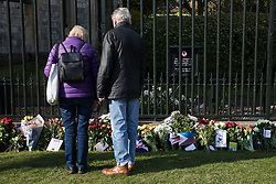 Windsor, UK. 16th April, 2021. Visitors look at floral tributes left by members of the public outside the Cambridge Gate to Windsor Castle on the eve of the funeral of the Duke of Edinburgh. The funeral of Prince Philip, Queen Elizabeth II's husband, will take place at St George's Chapel in Windsor Castle at 15:00 BST on 17th April.