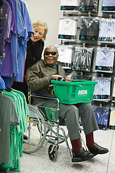 Volunteer carer helping visually-impaired wheelchair user to shop in supermarket choosing clothes, on a trip organised by a resource for people with physical and sensory impairment.