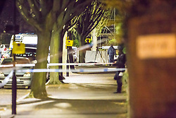 Forensics investigators stand by what appears to be a makeshift crime scene tent. Police have erected a cordon closing of a wide area surrounding the scene in Chestnut Avenue, Forest Gate, East London where an 18 year-old male was stabbed to death at around 11pm on Monday night. London, April 17 2018.