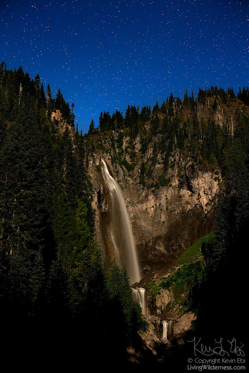 Comet Falls, so named because it resembles a comet's tail, glows underneath the night sky. The waterfall, which is located in Mount Rainier National Park, Washington, is lit by the full moon. Comet Falls, at 320 feet (98 meters), is one of the tallest waterfalls in the park.