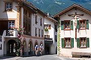 Cyclists pass a crucifix on a traditional house in Mustair, Switzerlan