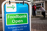 Swinging A-frame sign outside the Trussell Trust's Kingston Foodbank, Kingston, United Kingdom.  The sign directs people to the foodbank which provides emergency food to local people.  Two men are waiting outside the foodbank to receive their free food box which will contain basic non-perishable food for three days. In 2012-13 foodbanks fed 346,992 people nationwide. Of those helped, 126,889 were children. This form is used by a Trussell volunteer when preparing a food box for an adult.  In response to the Government cuts to welfare, foodbanks have experienced a significant increase in demand and in September 2013, Kingston foodbank provided food for their 5,000th person.