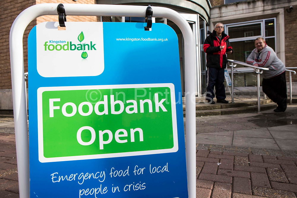 Swinging A-frame sign outside the Trussell Trust's Kingston Foodbank, Kingston, United Kingdom.  The sign directs people to the foodbank which provides emergency food to local people.  Two men are waiting outside the foodbank to receive their free food box which will contain basic non-perishable food for three days. In 2012-13 foodbanks fed346,992 people nationwide. Of those helped, 126,889 were children. This form is used by a Trussell volunteer when preparing a food box for an adult.  In response to the Government cuts to welfare, foodbanks have experienced a significant increase in demand and in September 2013, Kingston foodbank provided food for their 5,000th person.
