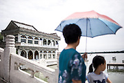 A Chinese woman with her daughter visits the stone teahouse protecting herself from the sun using an umbrella in Summer Palace in Beijing, China, July 21, 2014. <br /> <br /> Pale skin has historically been prized as beautiful in China, and the concept is widespread in other Asian countries. Besides health topics, beauty is one of the main reasons that makes protection from the sun's rays so important. <br /> <br /> © Giorgio Perottino