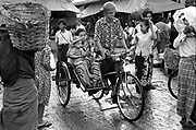 Mother and child ride throug the wet street in a cycle rickshaw. Rangoon, Burma 1997