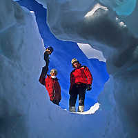 Staff at Adventure Network's Patriot Hills expediton base stand above a  snow cave they dug.