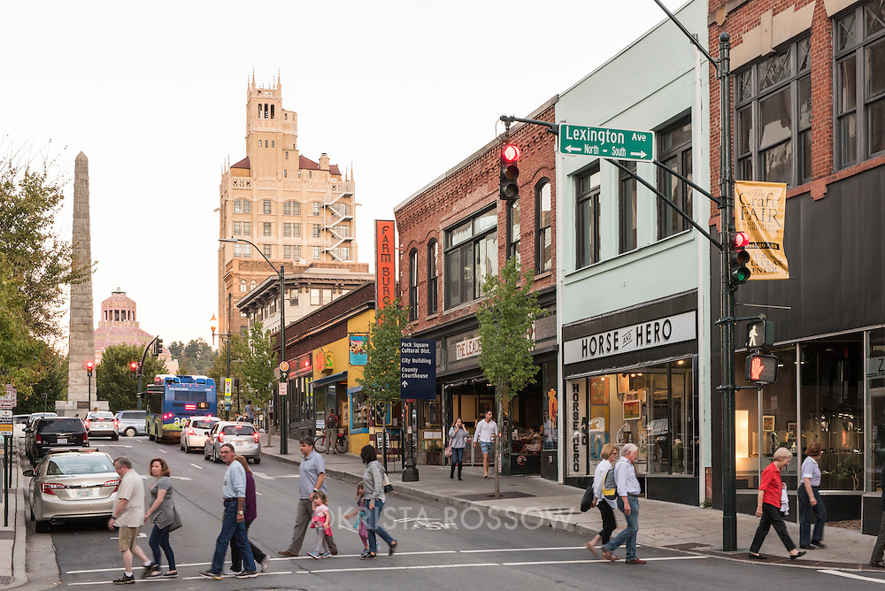 Busy late afternoon street scene in downtown Asheville, North Carolina, with iconic Art Deco buildings and the Vance Memorial obelisk in the background.