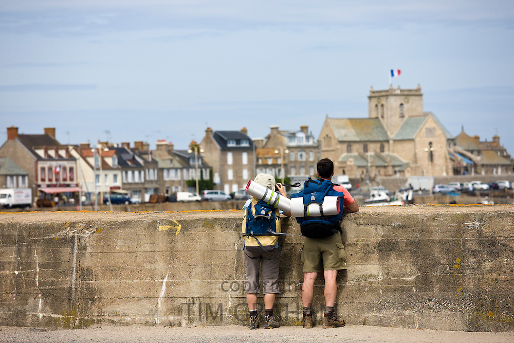 Tourist couple enjoying the view at Barfleur in Normandy, France