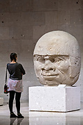 A tourist views a colossal Olmec stone head at the Museum of Anthropology in the historic center of Xalapa, Veracruz, Mexico. The Olmec civilization was the earliest known major Mesoamerican civilizations dating roughly from 1500 BCE to about 400 BCE.