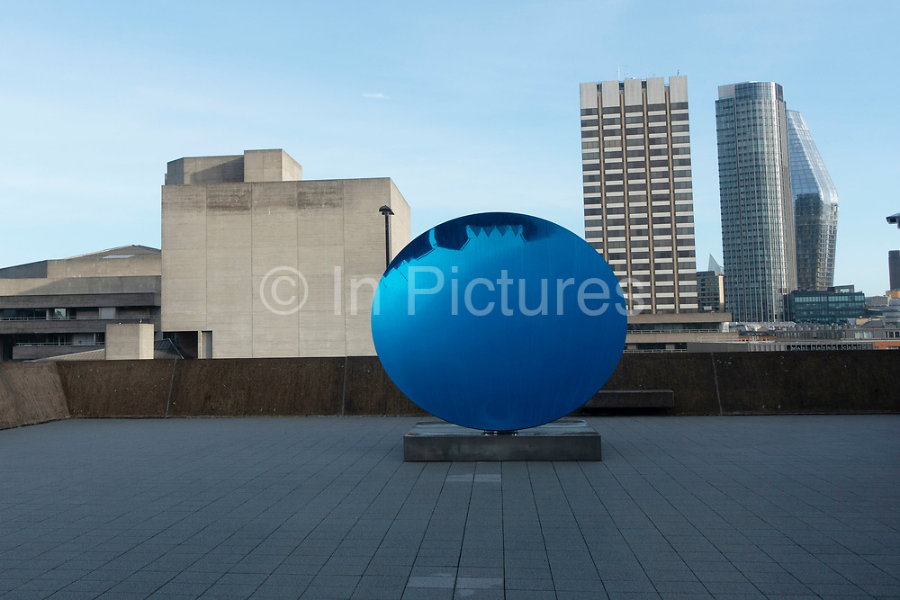 Visitors interacting with artworks at the Space Shifters exhibition at the Hayward Gallery on 16th December 2018 in London, United Kingdom. The exhibit was a major group show of sculptures and installations that explored perception and space, featuring 20 artists. Sky Mirror, Blue 2016 by Anish Kapoor.