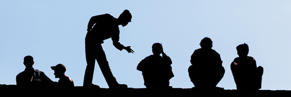 Six men in silhouette with one man pointing