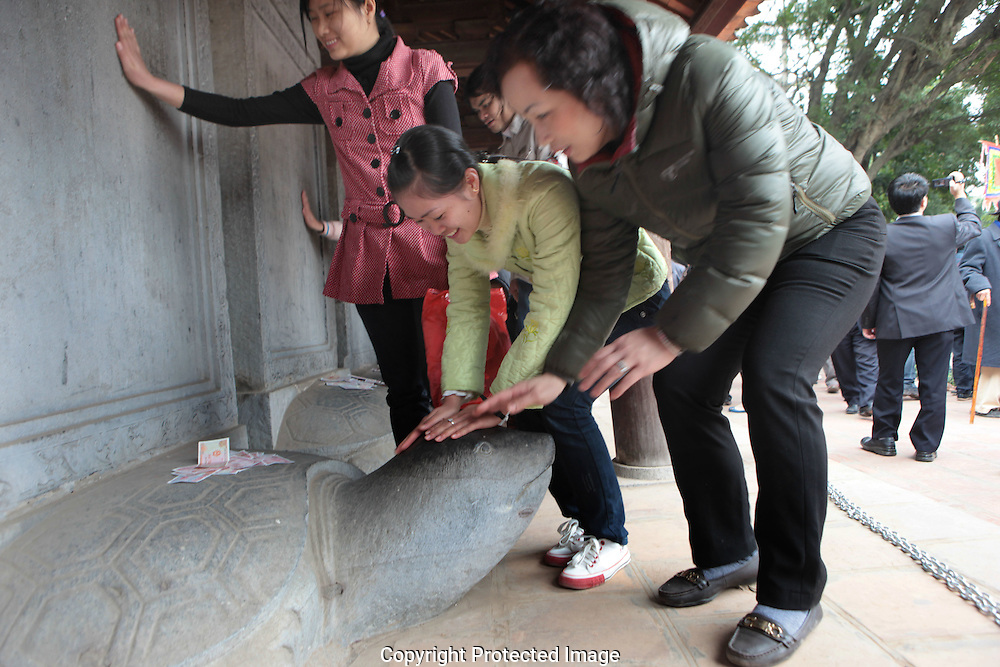 Youngsters pat a turtle for good luck at the Temple of Literature in Hanoi.  Photograph by Dennis Brack