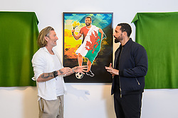 EMBARGOED TO 0001 FRIDAY JUNE 4 EDITORIAL USE ONLY Robbie Savage unveils a painting to Rio Ferdinand, depicting the former England footballer draped in a Welsh flag as part of a 'Hall of Fame' set up by Robbie and UEFA EURO 2020 Official Partner Heineken, ahead of this summer's tournament. Issue date: Friday June 4, 2021.