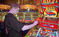 Young homeless man putting coin into slot machine in seaside arcade,