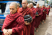 18 JUNE 2013 - YANGON, MYANMAR:  Burmese Buddhist monks on the daily alms rounds on a busy street in Yangon, Myanmar. Most Burmese men join the Sangha (Buddhist clergy) at least once in their lives. Sometimes for only a few weeks, others make a lifetime commitment.      PHOTO BY JACK KURTZ