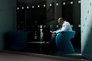 A businessman sits reading documents in sunlight by the window of a company foyer in the City of London, the capital's financial district. Seated in the foyer he has chosen the brightness in an otherwise dark location, where he can concentrate on reading the notes resting on his lap. A theme of small squares appear on the glass, currently popular in the City of London, the capital's oldest, financial district.