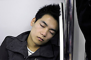 portrait of Asian young man during a commuting nap