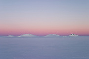 Four mountains seen across the Greenland ice cap illuminated by the midnight sun during a British mountaineering expedition to Knud Rasmussens Land, East Greenland, Arctic, 2006.