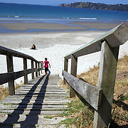 A young girl walks down a wooden staircase and onto Onetangi Beach, Waiheke Island, Auckland New Zealand,  2010 Photo Tim Clayton.