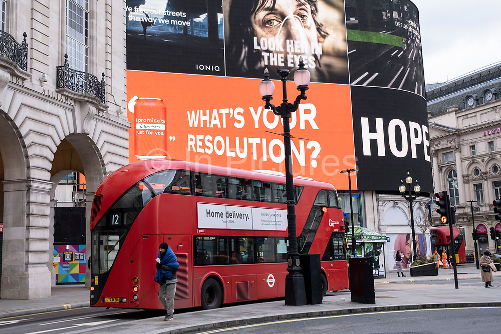 Homeless man collecting money from passing vehicles at Piccadilly Circus as the giant advertising screens show slogans of hope and the faces of coronavirus patients which are part of the latest NHS, Public Health England campaign to encourage people in Britain to take the virus seriously as the national coronavirus lockdown three continues on 29th January 2021 in London, United Kingdom. Following the surge in cases over the Winter including a new UK variant of Covid-19, this nationwide lockdown advises all citizens to follow the message to stay at home, protect the NHS and save lives.