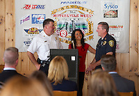 Laconia Fire Chief Kenneth Erickson and Laconia Police Captain Bill Clary are welcomed to the podium by Cynthia Makris of the Naswa Resort during the kickoff event for Motorcycle Week 2015 at the Faro Restaurant in Weirs Beach on Thursday morning.  (Karen Bobotas/for the Laconia Daily Sun)