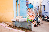 India, Jodhpur. A girl resting with her satchel.