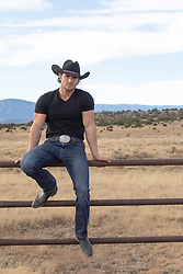 cowboy sitting on a fence in rural America
