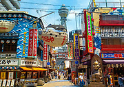 Shinsakei, Osaka. Famous Puffer fish, fugu, sign hanging with busy background of signs, bars, shops along main street in the entertainment area with the Tsutenkaku Tower i  the background