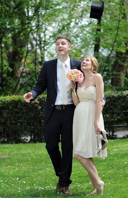 Braut und Bräutigam beobachten einen fallenden Zylinder nachdem sie ihn in die Luft geworfen haben   young couple on wedding day playing with a hat   