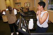 (MODEL RELEASED IMAGE). Every week, the Revis family (Rosemary on treadmill talking with Ron) faithfully trekked to the health club in the Wakefield Medical Center, a hospital complex in Raleigh, North Carolina, for two-hour exercise sessions. They enjoyed the workouts, but found them so time-consuming that they wound up eating more fast food than ever. Fearing its potential impact on their health, they ultimately gave up the club in favor of dining and exercising at home. (Supporting image from the project Hungry Planet: What the World Eats.)