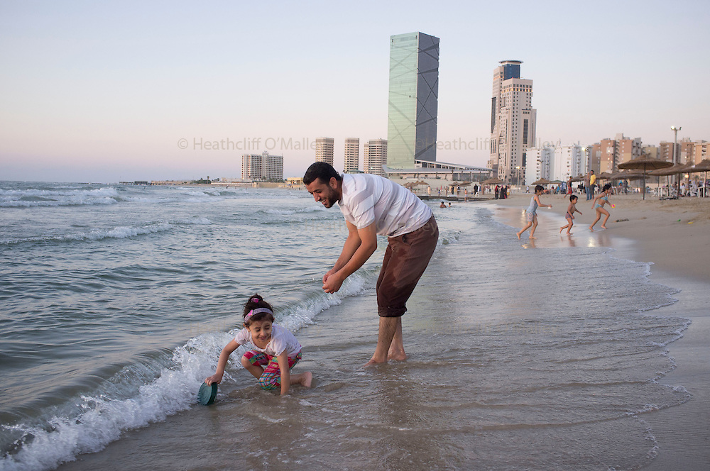 Sco0033837 .  Daily Telegraph..Libyan's enjoy Tripoli's beach as the sun sets on Friday evening. After two weeks of relative peace in the city it's residents now feel safe enough to take their children out on family outings...Tripoli 9 September 2011