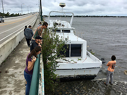 October 7, 2016 - Florida, U.S. - Residents check out a damaged boat along the Jenson Causeway in Jensen Beach on Friday morning. (Credit Image: © Richard Graulich/The Palm Beach Post via ZUMA Wire)