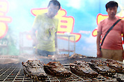 NANNING, CHINA - SEPTEMBER 05: (CHINA OUT) <br /> <br /> <br /> A man sells grilled crocodile meat during a food festival on September 5, 2013 in Nanning, Guangxi Province of China. <br /> ©Exclusivepix