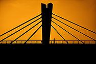 Silhouette of a man crossing a bridge