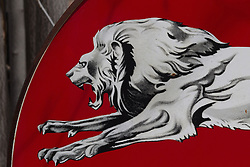 detail of a gas station sign with a hand painted lion