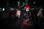 New York, NY - 31 October 2019. the annual Greenwich Village Halloween Parade along Manhattan's 6th Avenue. A calavera catrina is accompanied by a woman in Victorian costume.